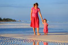Mother and little daughter walking on the beach Stock Images