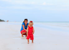 Mother and little daughter walking on the beach Royalty Free Stock Image