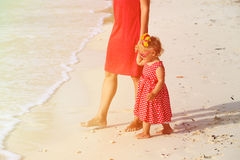 Mother and little daughter walking on beach Stock Photos