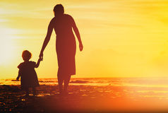 Mother and little daughter walking on beach at sunset. Mother and little daughter walking on sand beach at sunset Stock Image