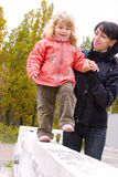 Mother with little daughter walking on railing Royalty Free Stock Photo