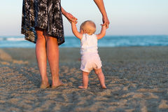 Mother and little daughter walking on sand beach at sunset Royalty Free Stock Photography