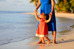 Mother and little daughter walking on summer beach. Mother and little daughter walking on summer tropical beach Royalty Free Stock Image