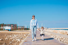 Mother and little daughter walking on summer beach. Mother and little daughter walking on summer tropical beach Royalty Free Stock Photography