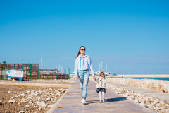 Mother and little daughter walking on summer beach. Mother and little daughter walking on summer tropical beach Stock Images
