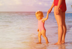 Mother and little daughter walking on sunset beach Stock Images