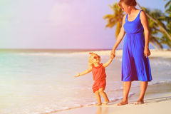 Mother and little daughter walking on tropical beach Stock Images