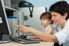 Mother with little daughter working on computer Royalty Free Stock Photos