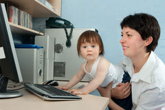 Mother with little daughter working on computer Stock Images