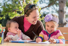 Mother And Little Daughters Drawing Pictures Together Outdoors I Stock Photo