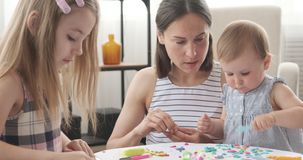 Mother and little daughters playing with plasticine. Mother with two little daughters making shapes from colorful plasticine at home stock video footage
