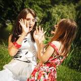 Mother and little girl blowing soap bubbles in park. Stock Photos
