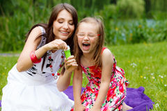 Mother and little girl blowing soap bubbles in park. Royalty Free Stock Image