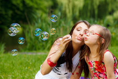 Mother and little girl blowing soap bubbles in park. Stock Image