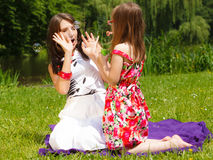 Mother and little girl blowing soap bubbles in park. Royalty Free Stock Photos