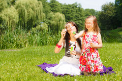 Mother and little girl blowing soap bubbles in park. Stock Images