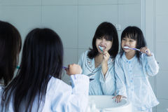 Mother and little girl brushing teeth Stock Photo