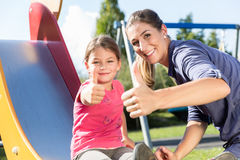 Mother and little girl chuting at adventure playground in park Royalty Free Stock Image