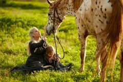 Mother with a little girl in dresses stroke a spotted horse royalty free stock photography