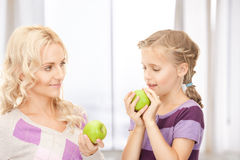 Mother and little girl with green apple Stock Photography