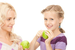 Mother and little girl with green apple Royalty Free Stock Photos
