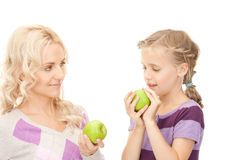 Mother and little girl with green apple Stock Photos