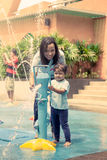 Mother and little girl having fun to play with water in park Royalty Free Stock Photo