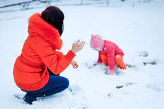 Mother and little girl having fun on winter day Stock Images