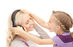 Mother and little girl with headphones Stock Photography