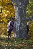 Mother and little girl hiding behind a tree. In a park in autumn. Tree of Platanus Stock Image