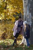 Mother and little girl hiding behind a tree. In a park in autumn. Tree of Platanus Royalty Free Stock Photo