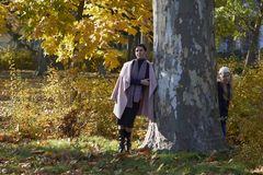 Mother and little girl hiding behind a tree. In a park in autumn. Tree of Platanus Stock Photography