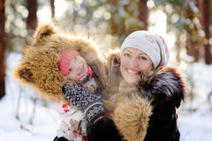 Mother and little girl laughing in winter forest Royalty Free Stock Images