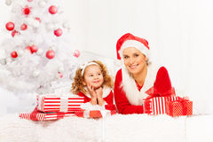 Mother and little girl lay under Christmas tree Royalty Free Stock Photos
