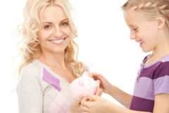 Mother and little girl with piggy bank Royalty Free Stock Images