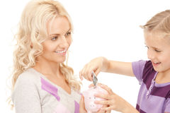 Mother and little girl with piggy bank Stock Photos
