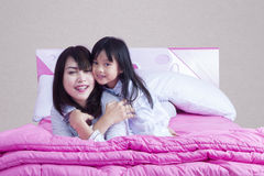 Mother and little girl play on bed Royalty Free Stock Photography