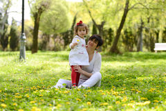Mother and little girl playing in the park Stock Images