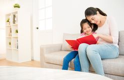 Mother and little girl reading a book stock images