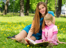 Mother and little girl reading book together Stock Photography