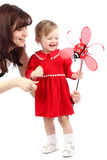 Mother and little girl in a red dress playing with toy Royalty Free Stock Image