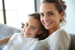 Mother with little girl relaxing on sofa. Mom with little girl reading book in sofa Royalty Free Stock Image