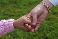 Mother and little girl's hands with green garden background Stock Photo