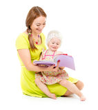 Mother and little girl sitting and reading book together Stock Images