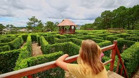 Mother Little Girl Stand on Bridge above Labyrinth in Park. Caucasian mother little blond girl with pigtail stand on wooden watch bridge above hedge labyrinth in stock video