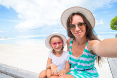 Mother and little girl taking self portrait at tropical vacation Stock Photos