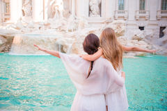 Mother and little girl at Trevi Fountain, Rome. Little girl making a wish to come back. Royalty Free Stock Photo