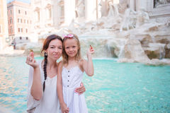Mother and little girl trowing coin at Trevi Fountain, Rome for good luck. Little girl making a wish to come back. Royalty Free Stock Photos