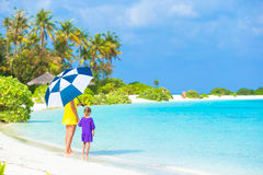 Mother and little girl with umbrella hiding from Stock Photo