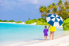 Mother and little girl with umbrella hiding from Royalty Free Stock Images
